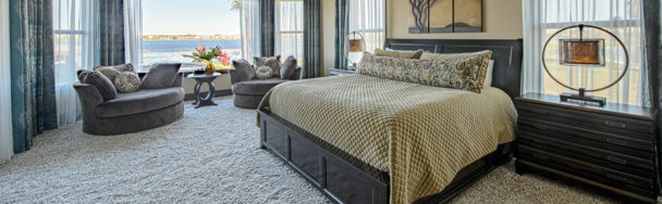 This master bedroom has spacious sleeping and living area with beautiful window treatments.