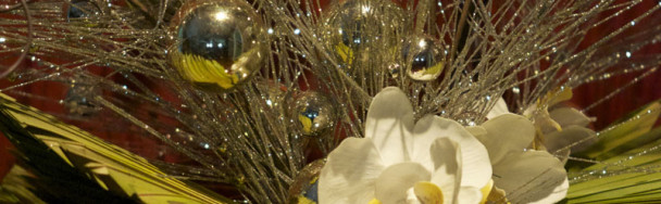 This shows a close up view of a custom floral arrangement using silver branches and ornaments with orchids and dried palm fronds