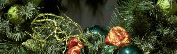 This shows a traditional holiday wreath mixing permanent exotic fruit with ornaments
