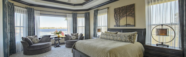 This shows Custom Window Treatments that frame the lakeside view of this Master Bedroom
